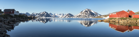 Greenland, Sermersooq, Kulusuk, Schweizerland Alps, mountains and wooden huts at the shore reflecting in water - ALRF00998