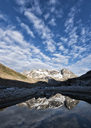 Greenland, Sermersooq, Kulusuk, Schweizerland Alps, man standing at lake with mountains reflecting in water - ALRF01001