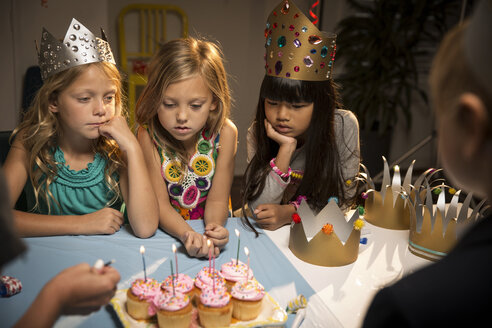 High angle view of children looking at cup cakes on table - CAVF04100