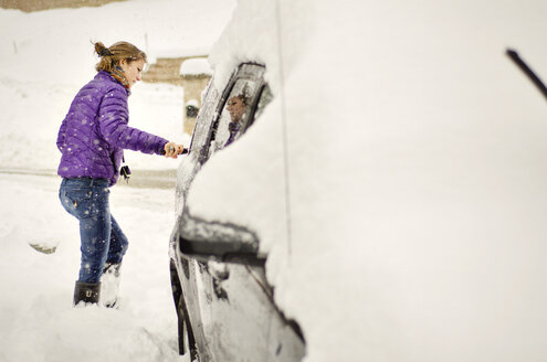 Woman cleaning snow on car - CAVF04112