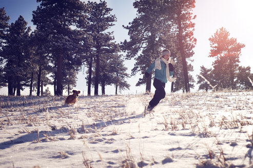 Playful woman with dog running on snow covered field - CAVF04124