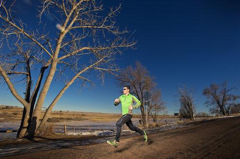 Man jogging on field against clear blue sky - CAVF04130