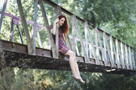 Redheaded young woman sitting barefoot on footbridge in nature - JSMF00118