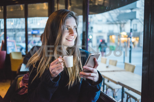 Paris, France, portrait of smiling young woman with smartphone drinking espresso in a coffee shop - AFVF00292
