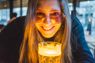 Paris, France, portrait of happy young woman with glass of beer in a pub in the evening - AFVF00295
