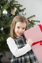 Portrait of smiling little girl holding Christmas present - LVF06776