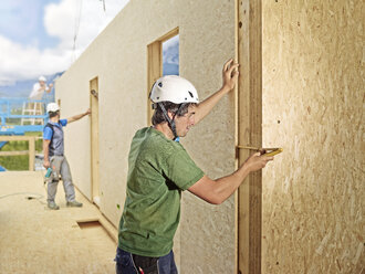 Austria, worker checking flakeboard with pocket rule - CVF00272