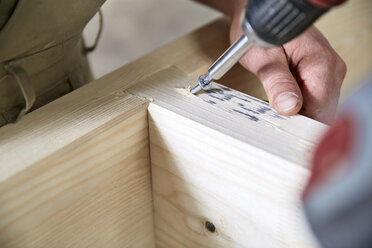 Carpenter fixing wooden construction with portable drill - CVF00290