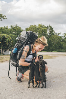 Cuba, young woman with backpack stroking young dogs, laughing - GUSF00536