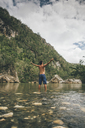 Cuba, Baracoa, Young man standing in Yumuri river, rear view - GUSF00560