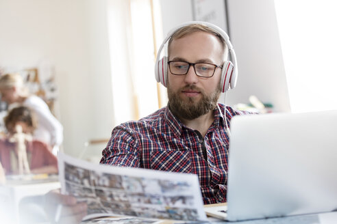 Design professional listening to music with headphones reviewing proofs at laptop - CAIF09233