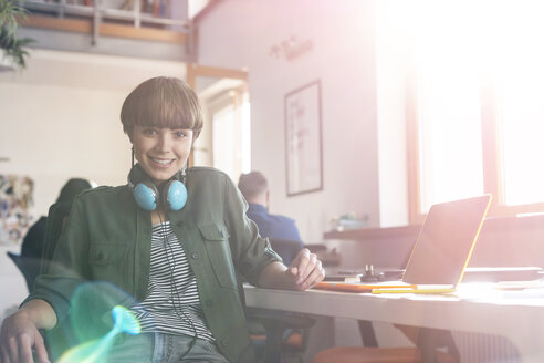Portrait smiling female design professional with headphones at laptop in office - CAIF09245