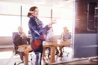 Businesswoman leading meeting at television screen in sunny conference room - CAIF09296
