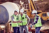 Construction workers meeting, using digital tablet at construction site - CAIF09305