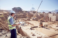Construction worker foreman using walkie-talkie at sunny construction site - CAIF09308