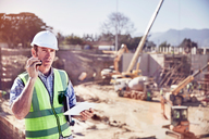 Construction worker foreman talking on walkie-talkie at sunny construction site - CAIF09311