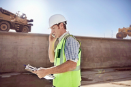 Construction worker foreman talking on cell phone at sunny construction site - CAIF09314