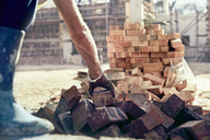 Construction worker bricklaying at construction site - CAIF09323