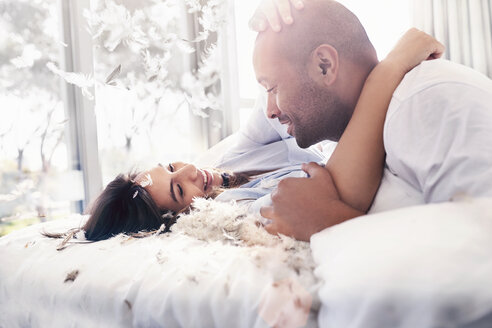 Pillow feathers falling around playful, affectionate couple on bed - CAIF09326