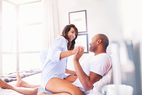 Smiling, playful couple on bed - CAIF09332