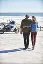 Affectionate senior couple walking on sunny beach toward motorcycle - CAIF09335