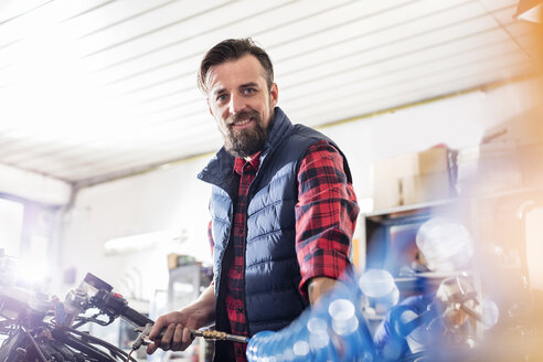 Portrait confident male motorcycle mechanic working in workshop - CAIF09368