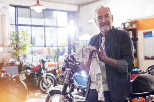 Portrait smiling senior male motorcycle mechanic wiping hands on rag in workshop - CAIF09371