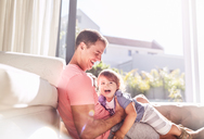 Affectionate father holding baby son in sunny living room - CAIF09389
