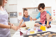Mother and children baking cookies in kitchen - CAIF09398