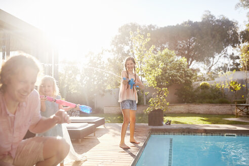 Daughter with squirt gun spraying father with water at sunny summer poolside - CAIF09401