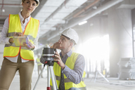Engineers with digital tablet and theodolite surveying construction site - CAIF09407