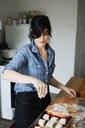 Woman sprinkling flour on cookies - CAVF04457