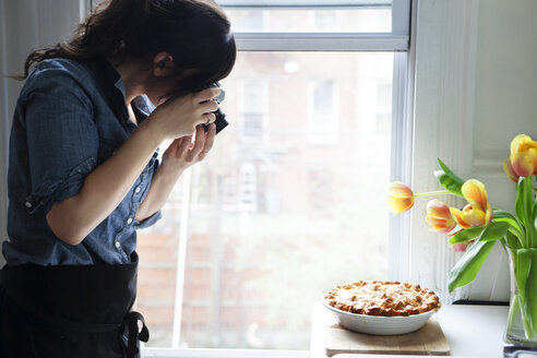 Woman photographing baked pie - CAVF04463