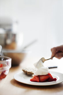 Cropped image of hand adding cream to strawberries - CAVF04469