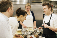 Chef showing ingredient to students at commercial kitchen - CAVF04520