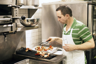 Man preparing food at barbeque grill at commercial kitchen - CAVF04526