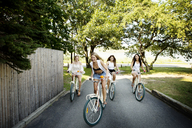 Playful friends cycling on road - CAVF04622