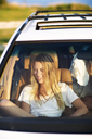 Smiling woman looking away while sitting in car - CAVF04643