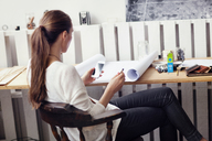 Side view of woman using smart phone while sitting on chair at home - CAVF04667