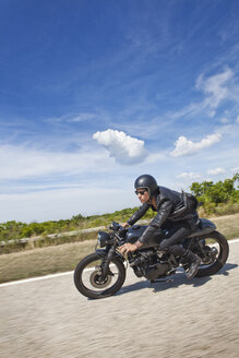 Man riding motorcycle on road against cloudy sky - CAVF04691