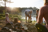 Grandparents and grandchildren at campfire at sunny lakeside in woods - CAIF09416