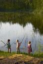 Girls fishing at sunny lakeside - CAIF09419