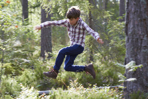 Energetic boy jumping in woods - CAIF09422