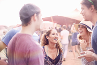Young friends hanging out talking at music festival - CAIF09461