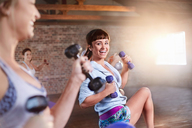 Smiling young women with dumbbells in exercise class gym studio - CAIF09479