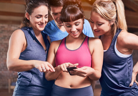 Young women and man in sports clothing texting with cell phone - CAIF09485