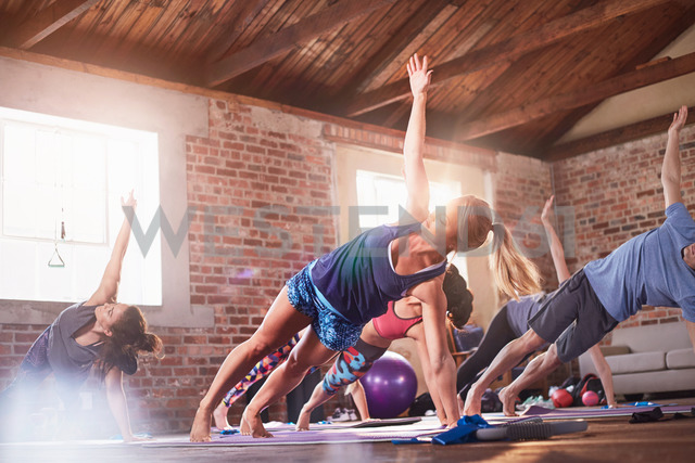 Exercise class doing side planks with arms outstretched in gym studio - CAIF09515
