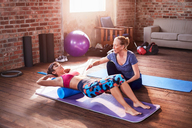 Fitness instructor helping young woman doing push-ups in gym studio - CAIF09521