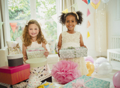 Portrait smiling girls holding birthday gifts - CAIF09533