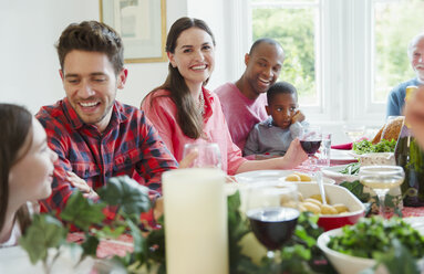 Portrait smiling woman enjoying Christmas dinner with family at table - CAIF09536